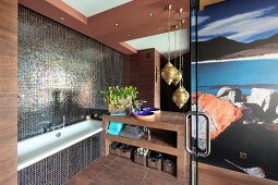 Bathtub next to washstand and brass pendant lamps in designer bathroom with mosaic tiles