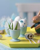 Eggs in egg cups on tray decorated for Easter