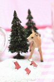 Christmas arrangement of miniature fir trees, deer figurine and stockings in artificial snow