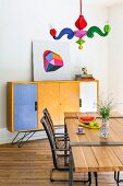 Postmodern pendant lamp with colourful arms above dining table with wooden top mounted on metal frame, metal armchairs and sideboard with colourful doors in background
