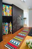 Brightly patterned rug on tiled floor and chalk drawings on wall painted with chalkboard paint