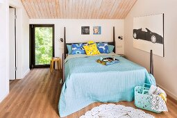 Turquoise bedspread on double bed with corner posts in modern bedroom with wood-clad ceiling