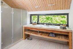Washstand with twin sinks on long wooden counter in modern bathroom