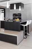 Multifunctional units, breakfast bar with bar stools, integrated, low sideboard and pendant lamps in designer kitchen