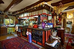 Crammed kitchen counter with antique cooker in open-plan interior