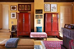 Two red-painted cupboards, ottomans and pictures in rustic bedroom with yellow wall