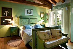 Painted wooden bed and bench in rustic bedroom with green walls
