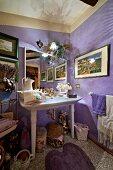 Elegant washstand against lilac walls in crammed bathroom
