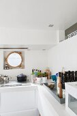 White kitchen counter with hob below porthole window of houseboat
