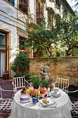 Autumnal arrangement on table and graceful antique chairs in courtyard of manor house