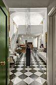 Chequered floor and modern pendant lamps in elegant foyer seen through open door