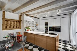 Designer fitted kitchen in rustic interior with whitewashed wooden ceiling and antique architectural element in wall to one side