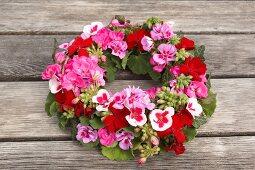 Kranz aus Geranienblüten auf Holztisch im Freien