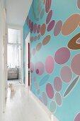 Light blue wall with geometric pattern in narrow hallway