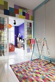 Laundry rack on colourful rug in front of glass sliding doors