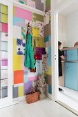 Colourful patchwork pattern on wall and view of woman in front of pale blue cabinet through open door