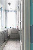Shimmering silver surfaces in narrow bathroom
