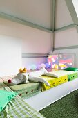 Colourful floor cushions and soft toys in seating area in child's attic bedroom