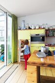 Yellow kitchen cabinets next to sliding terrace doors with child in front of open fridge