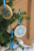 Small slices of tree trunk painted with blue and white star motifs hung from fir branches with blue ribbon