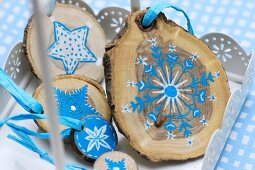 Christmas decorations made from small slices of tree trunk painted with blue and white stars