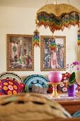 Various brightly patterned scatter cushions on bench, dining table and two Oriental pictures on wall