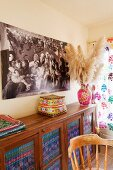 Ethic ornaments on wooden sideboard with brightly coloured fabric behind glass door panels below photo of hippie family