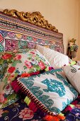 Bed headboard covered in colourful fabric and ethnic-style scatter cushions