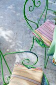 Green, vintage-style metal chairs with striped seat cushions