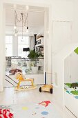 Rocking horse in white, child's bedroom with view into living room