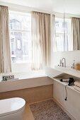 Bright, modern bathroom with custom washstand and fitted bathtub next to window