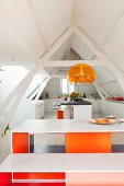 Designer table and bench set with brightly-painted inner sides below pendant lamp in open-plan kitchen