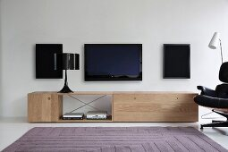 Table lamp on designer sideboard below speakers and flatscreen TV on white wall