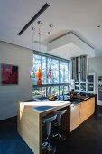 Designer breakfast bar with white bar stools and island counter in front of glass wall
