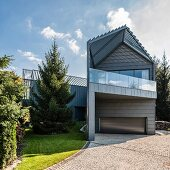 Metal-clad facade of modern, architect-designed house with garage door and roofed balcony