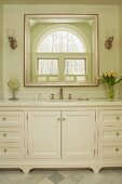 Washstand with marble counter below elegant mirror on wall