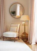 Upholstered chair below round mirror on wall in corner of elegant bedroom