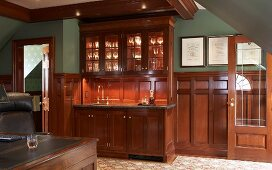 Smoking room with panelled wainscoting and glasses under spotlights in elegant, glass-fronted cabinet