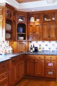 Elegant country-house kitchen with exotic wood cabinets and glass-fronted wall units