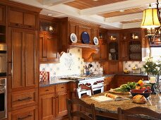 Kitchen-dining room with wooden fronts and wall units in cosy, country-house interior
