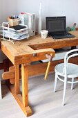 Old workbench used as vintage-style desk and white Thonet chair