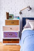 Tower of drawers with different fronts and handles as bedside cabinet against whitewashed brick wall