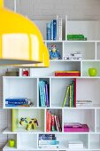 Books and colourful ornaments on white shelves; yellow pendant lamp in foreground
