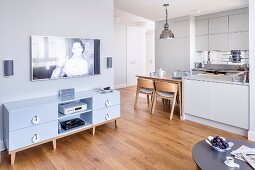 Flatscreen TV above media cabinet with fitted kitchen and integrated dining area in background