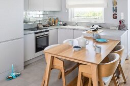 Pale wood dining area integrated into fitted kitchen