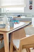 Dining table and designer, pale wood shell chairs in open-plan kitchen