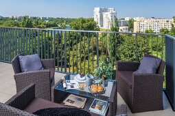 Outdoor furniture made from synthetic wicker on balcony with view over park landscape and high-rise buildings