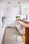 Designer kitchen with smooth, white doors and engineered wood counter