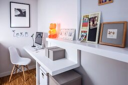 Plastic Chair at small, fitted desk with pictures on integrated floating shelf