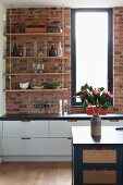 Open-fronted, suspended shelves against brick wall above white base units and blue island counter in open-plan kitchen